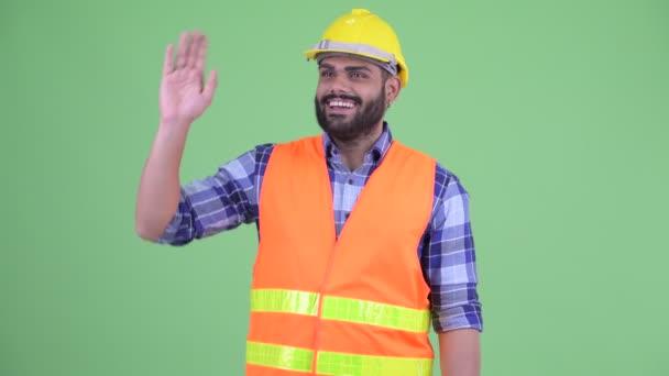 Šťastný mladý nadtloušatý vousáč indický stavební pracovník mávající ruku