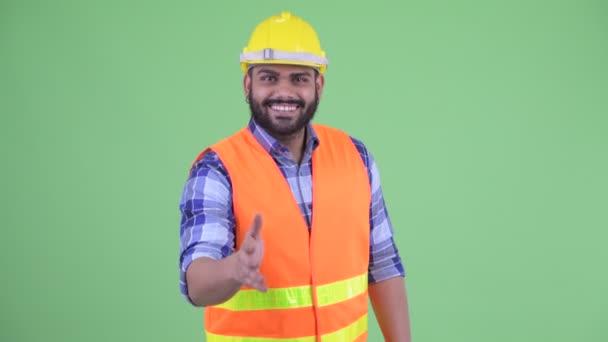 Šťastný mladý nadtloušatý vousáč indický stavební pracovník, který dává ruku
