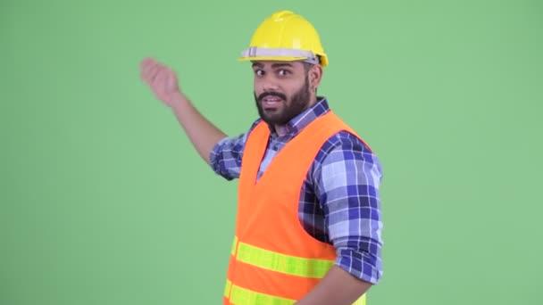 Šťastný mladý nadtloušatý vousáč indický stavební pracovník, který prezentuje něco
