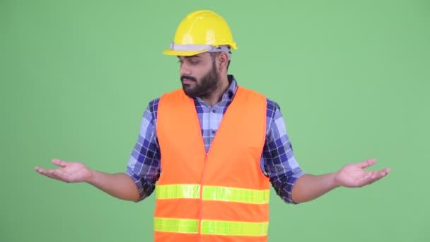 Šťastný mladý nadtloušatý vousáč indický stavební pracovník porovnávající něco