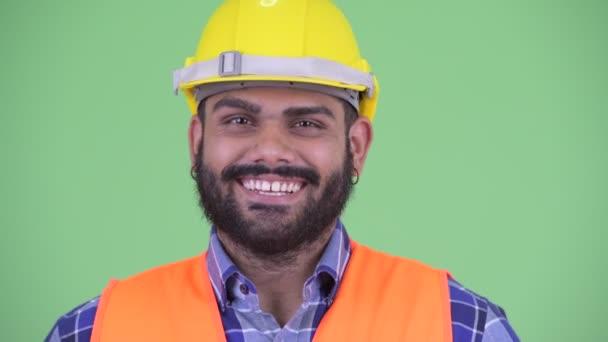 Tváří v tvář šťastného mladému nadváze vousatý muž na stavební práce pokyvuje hlavou Ano