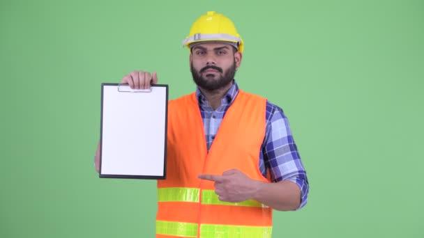 Šťastný mladý nadtloušatý vousáč indický stavební pracovník zobrazující schránku a zdvihové palce