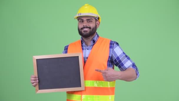 Šťastný přetloušatý vousatý muž stavební pracovník držící tabuli a zdvihové palce