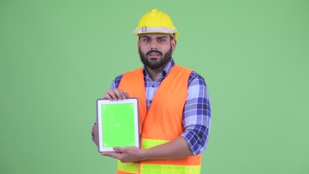 Šťastný mladý nadtloušatý vousáč indický stavební pracovník při zobrazování digitálního tabletu