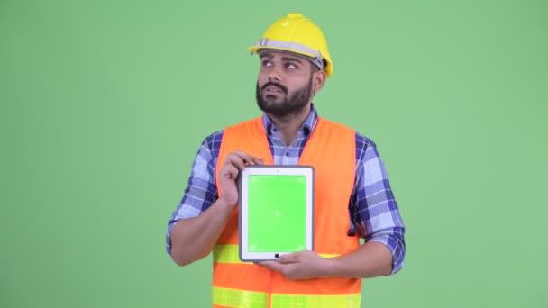 Šťastný mladík nadváha vousatý indický stavební pracovník myšlení při zobrazení digitálního tabletu