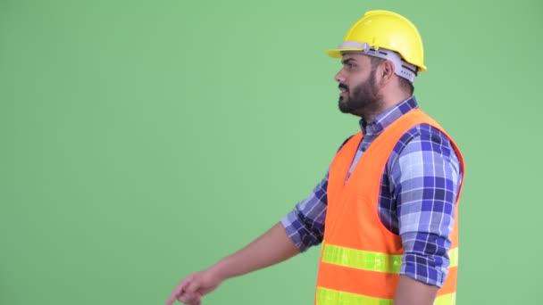 Pohled na profil šťastného mladého nadváhy vousatý muž stavební pracovník ukazující prst