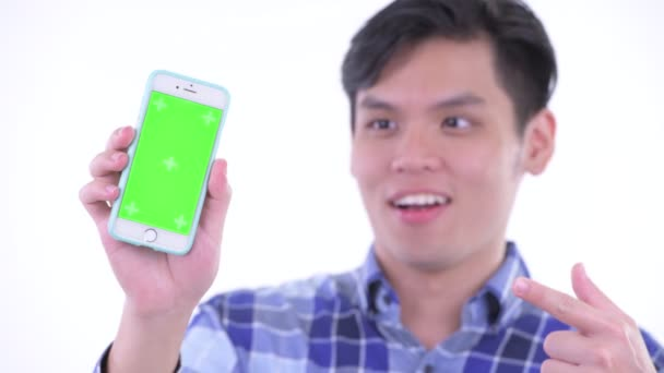 Tvář šťastného mladého asijského hipstera, který ukazoval telefon a dává palce