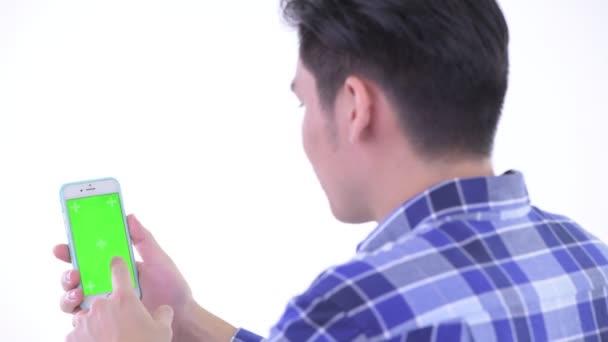 Closeup pohled na mladého asijského hipstera, který používá telefon
