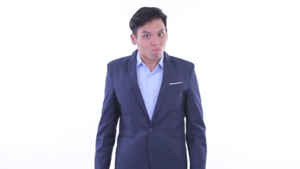 Angry young Asian businessman giving thumbs down
