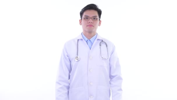 Happy young Asian man doctor smiling with arms crossed