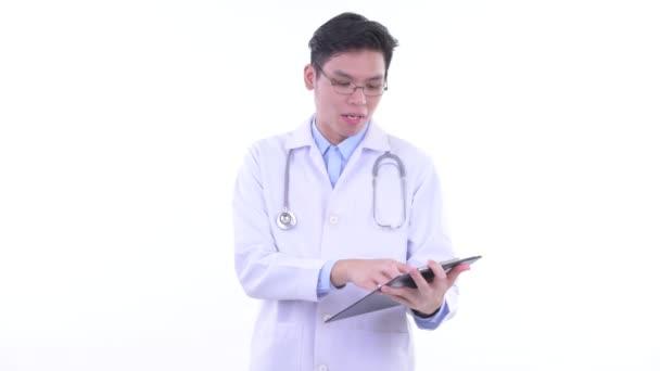 glücklich junge asiatische Mann Arzt sprechen, während Lesen auf Klemmbrett
