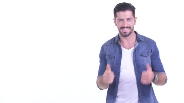 Happy young bearded hipster man touching something and giving thumbs up