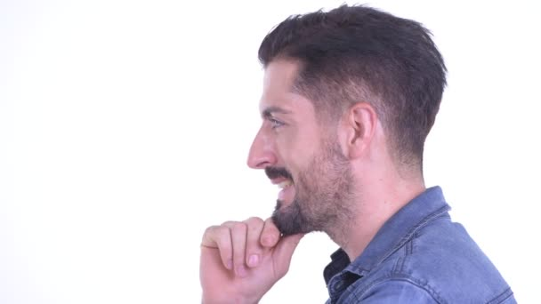 Closeup profile view of happy young bearded hipster man thinking