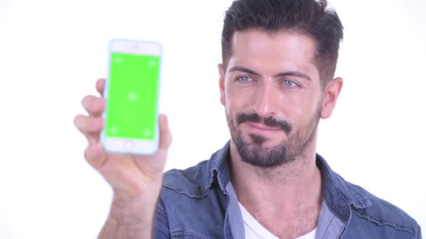 Face of happy young bearded hipster man showing phone