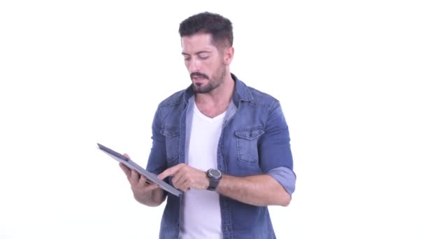 Happy young bearded hipster man using digital tablet
