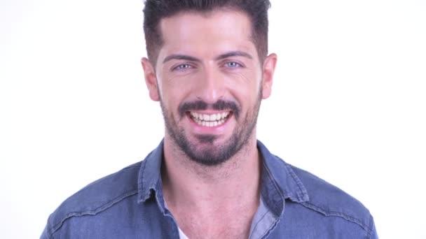 A boldog, fiatal, szakállas hipszter férfi arca mosolyog