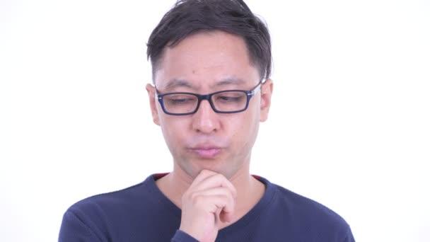 Gesicht eines gestressten japanischen Hipsters, der denkt und nach unten schaut