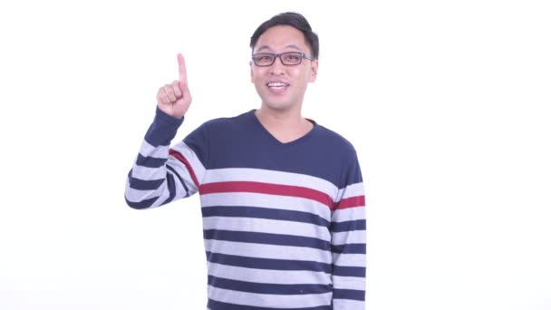 Happy Japanese hipster man with eyeglasses pointing up