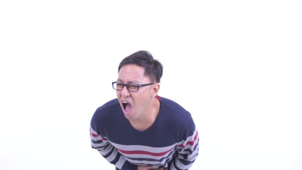 Stressed Japanese hipster man with eyeglasses having stomachache