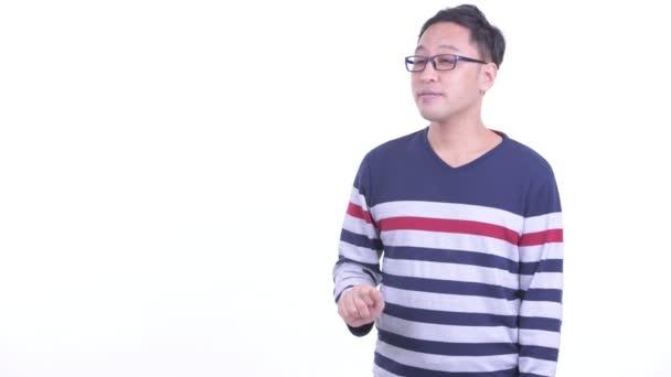 glücklicher japanischer Hipster-Mann, der etwas berührt und Daumen nach oben gibt
