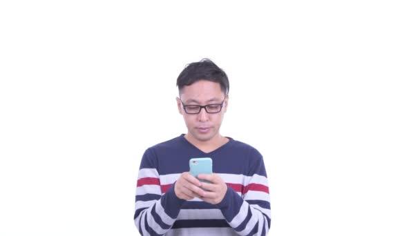 Felice uomo hipster giapponese usando il telefono e guardando sorpreso