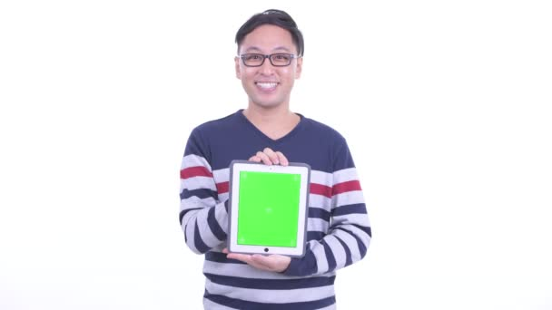 Happy Japanese hipster man talking while showing digital tablet