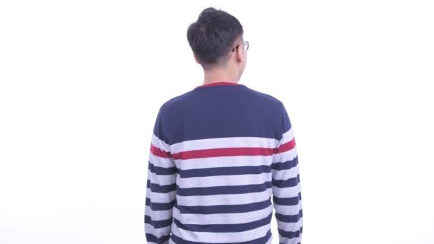 Rear view of Japanese hipster man thinking and looking around