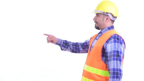 Pohled na profil šťastného vousatého muže stavební pracovník ukazující prstem