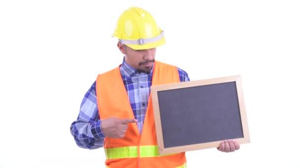 Ve stresu, vousatý muž stavební práce držící tabuli a palec