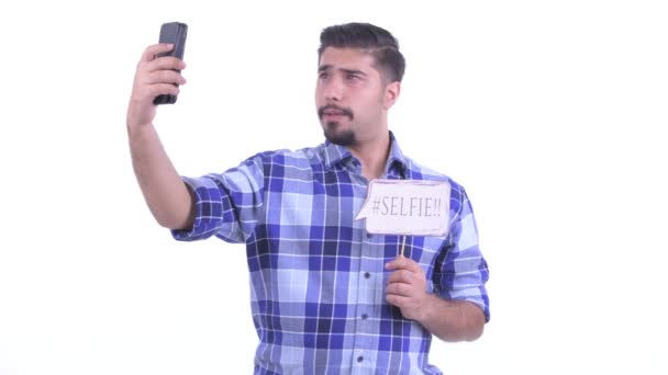Happy bearded Persian hipster man taking selfie with paper sign