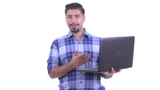 Happy bearded Persian hipster man talking while using laptop