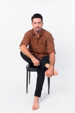 Full body shot of handsome bearded hipster man sitting on chair
