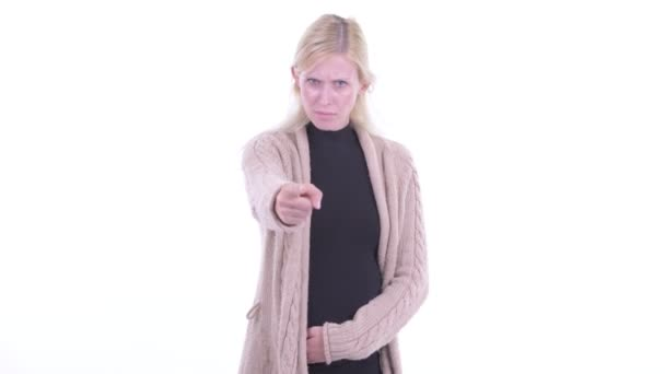 Angry young blonde pregnant woman pointing at camera
