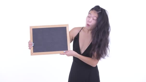 Happy beautiful Asian woman holding blackboard and looking surprised