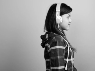Young beautiful Indian woman listening to music against gray background
