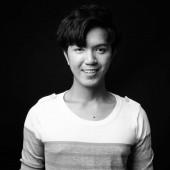 Mladý pohledný asijský muž s úsměvem na černém pozadí