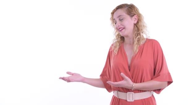 Šťastná krásná blondýnka podnikatelka mluví, zatímco ukazuje něco