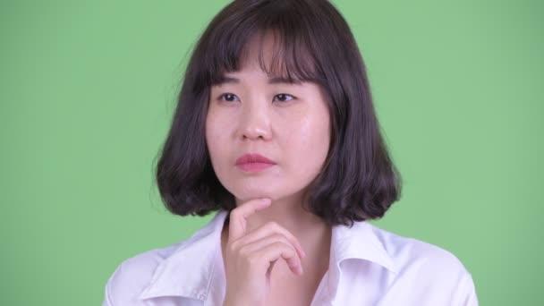 Tvář šťastné asijské podnikatelky myšlení a vzhlíží