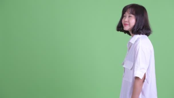 Profile view of happy beautiful ázsiai üzletasszony mosolygós