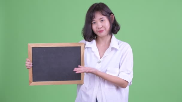 Happy Asian businesswoman holding blackboard and giving thumbs up