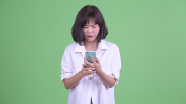 Stressed Asian businesswoman using phone and getting bad news