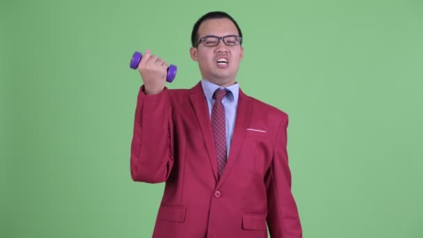 Funny Asian businessman with eyeglasses exercising with dumbbells