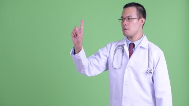 Šťastný asijský muž lékař dotýká něco