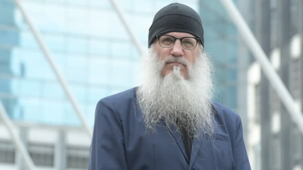 Face of mature bearded businessman wearing beanie and eyeglasses in the city outdoors