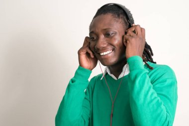 Face of happy young handsome African man with dreadlocks listening to music