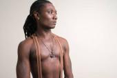 Junge gut aussehende muskulöse afrikanische Mann mit Dreadlocks denken hemdlos
