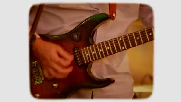 ruka hraje na elektrickou kytaru. 8mm film retro styl