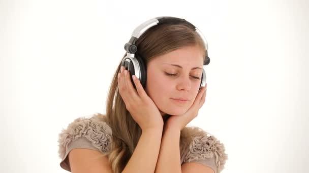 Mädchen hört Musik über Kopfhörer und bedeckt ihr Gesicht mit den Händen