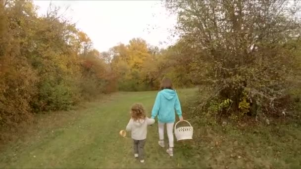 Children holding hands walking in an autumn forest