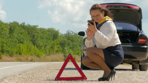 woman talking on the phone next to the warning triangle